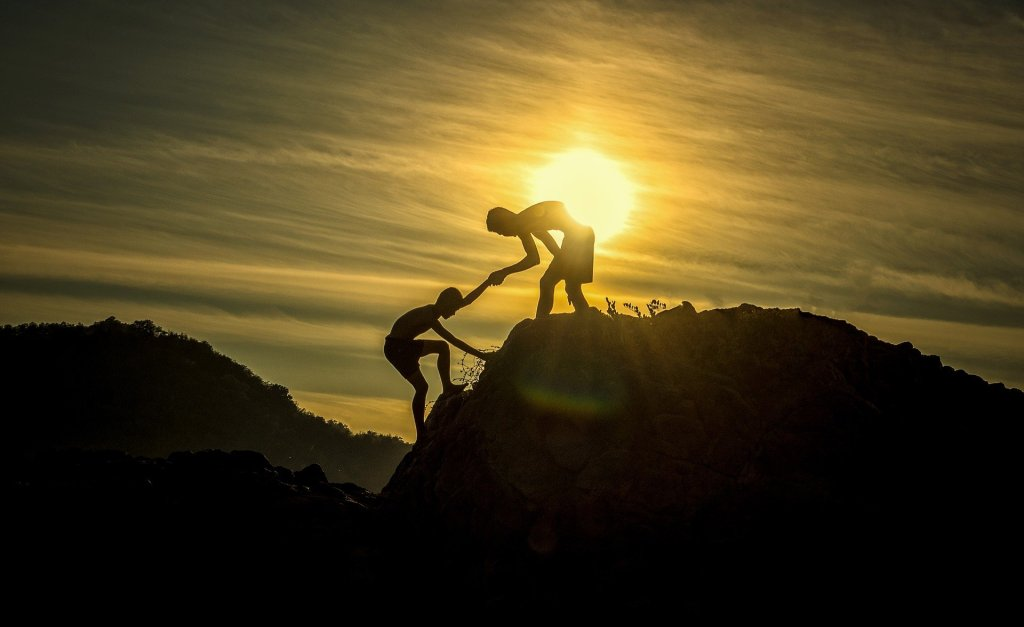 Man lends hand to another man up mountain at sunset
